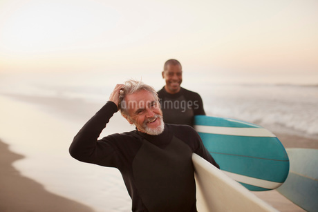 Older surfers carrying boards on beachの写真素材 [FYI02183615]