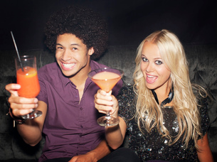 Portrait of enthusiastic couple toasting cocktails in nightclubの写真素材 [FYI02183648]