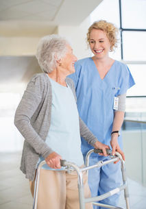 Senior patient with walker smiling at nurse in hospital corridorの写真素材 [FYI02183671]
