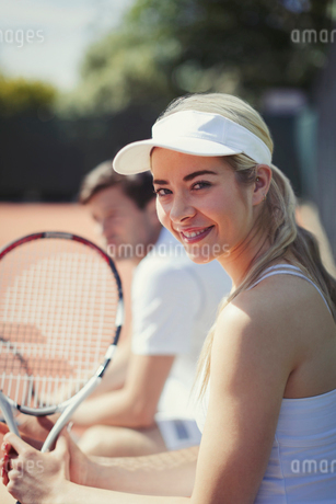 Portrait smiling, confident young female tennis player holding tennis racket on sunny tennis courtの写真素材 [FYI02183679]