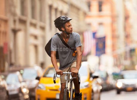 Man riding bicycle on city streetの写真素材 [FYI02183683]