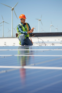 Engineer with equipment inspecting solar panels at sunny power plantの写真素材 [FYI02183713]