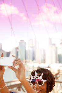 Woman in novelty sunglasses taking picture by city cityscapeの写真素材 [FYI02183720]