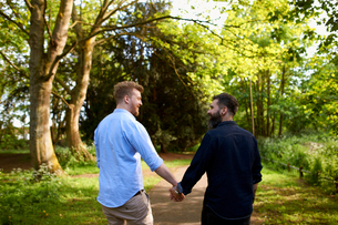 Affectionate male gay couple holding hands in sunny parkの写真素材 [FYI02183738]