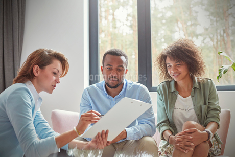 Female therapist with clipboard talking to couple in couples therapy sessionの写真素材 [FYI02183791]
