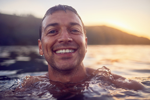 Close up portrait smiling, carefree man swimming in oceanの写真素材 [FYI02183800]