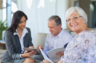 Financial advisor talking to couple on sofaの写真素材 [FYI02183856]
