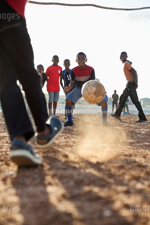 Boys playing soccer together in dirt fieldの写真素材 [FYI02183881]