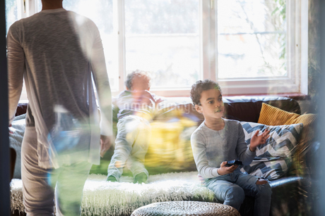 Boy with remote control watching TV in living roomの写真素材 [FYI02183895]
