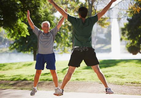 Older men doing jumping jacks outdoorsの写真素材 [FYI02183924]