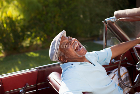 Laughing older man driving convertibleの写真素材 [FYI02183929]