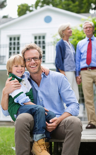 Father and son smiling outside houseの写真素材 [FYI02183932]