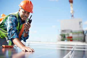 Engineer with walkie-talkie inspecting solar panel at power plantの写真素材 [FYI02183995]