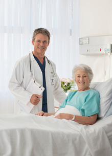 Portrait of smiling doctor and senior patient in hospital roomの写真素材 [FYI02184027]