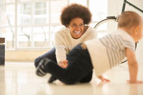 Mother watching baby boy crawl on living room floorの写真素材 [FYI02184034]