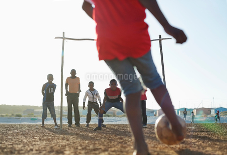 Boys playing soccer together in dirt fieldの写真素材 [FYI02184052]