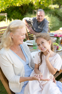Older woman sitting with granddaughter outdoorsの写真素材 [FYI02184053]