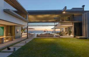 Illuminated modern, luxury home showcase courtyard and houseの写真素材 [FYI02184064]