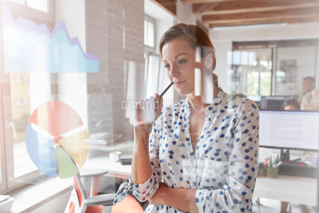 Pensive businesswoman reviewing graph and pie chart on window in officeの写真素材 [FYI02184070]