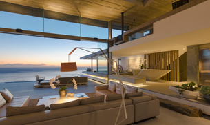 Illuminated modern, luxury home showcase interior living room with ocean view at duskの写真素材 [FYI02184095]