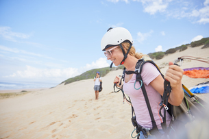 Smiling female paraglider with equipment on beachの写真素材 [FYI02184124]