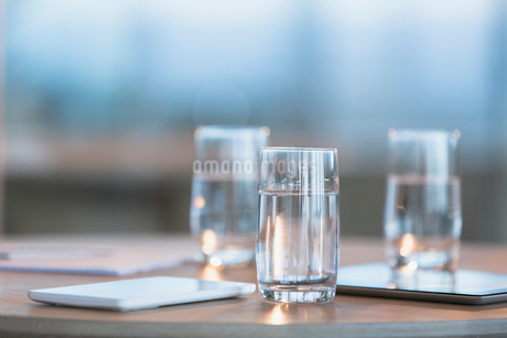 Water in glasses next to digital tablets on tableの写真素材 [FYI02184127]