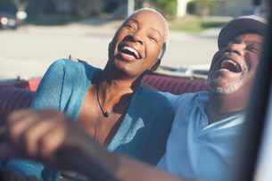 Older couple laughing in convertibleの写真素材 [FYI02184141]