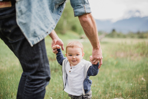 Father walking with baby son in grassy fieldの写真素材 [FYI02184156]