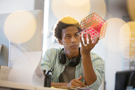 Businessman examining cube at desk in officeの写真素材 [FYI02184170]