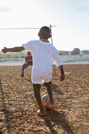 Boys playing soccer together in dirt fieldの写真素材 [FYI02184193]