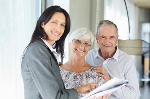 Financial advisor talking to couple indoorsの写真素材 [FYI02184206]
