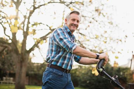 Portrait smiling senior man mowing lawnの写真素材 [FYI02184246]
