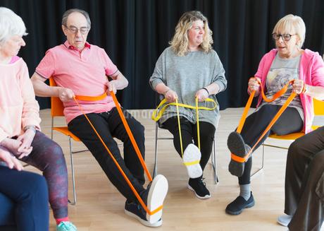 Active seniors exercising in circle, using straps to stretch legsの写真素材 [FYI02184293]