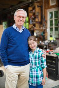 Man and granddaughter smiling in garageの写真素材 [FYI02184310]