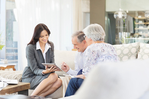Financial advisor using tablet computer with clientsの写真素材 [FYI02184340]