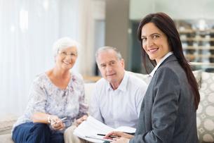 Financial advisor talking to couple on sofaの写真素材 [FYI02184352]