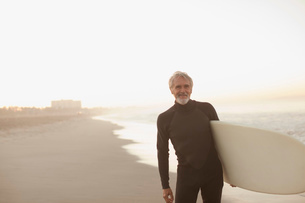 Older surfer carrying board on beachの写真素材 [FYI02184380]