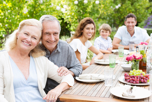 Family smiling at table outdoorsの写真素材 [FYI02184385]