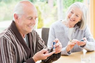 Older couple testing blood sugar togetherの写真素材 [FYI02184410]
