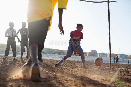 Boys playing soccer together in dirt fieldの写真素材 [FYI02184449]