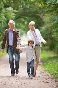 Couple walking with grandson on rural roadの写真素材 [FYI02184467]