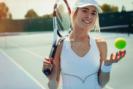 Portrait smiling, confident young female tennis player holding tennis racket and tennis ball on tennの写真素材 [FYI02184473]
