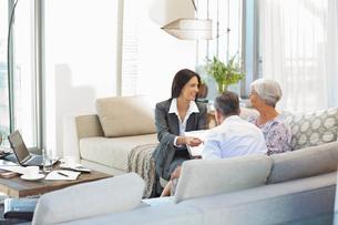 Financial advisor talking to couple on sofaの写真素材 [FYI02184486]