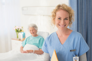 Portrait of smiling nurse with senior patient in backgroundの写真素材 [FYI02184488]