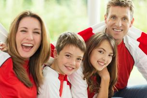 Family in sports jerseys cheering in living roomの写真素材 [FYI02184490]