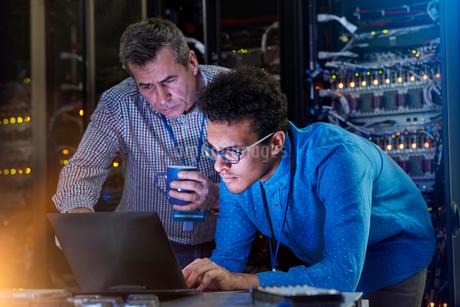 Focused male IT technicians working at laptop in dark server roomの写真素材 [FYI02184499]