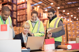 Businesswoman and workers using laptop in warehouseの写真素材 [FYI02184506]