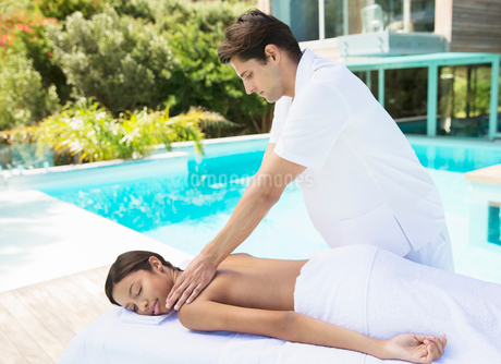 Woman receiving massage poolside at spaの写真素材 [FYI02184521]