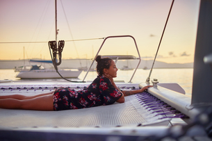 Serene young woman relaxing on catamaran net at sunsetの写真素材 [FYI02184524]