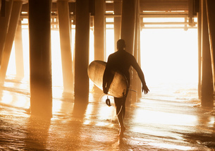 Older surfer carrying board under pierの写真素材 [FYI02184563]